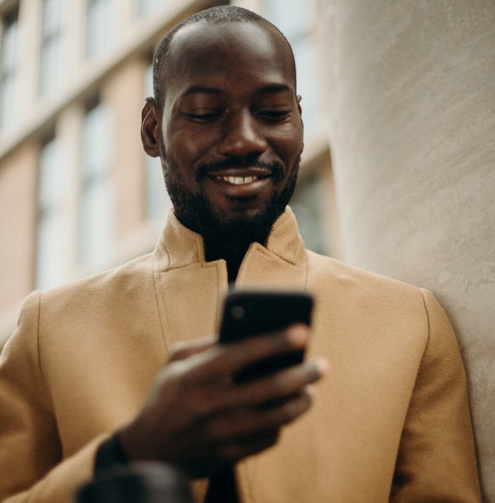 A black man using a smartphone to pay for DStv